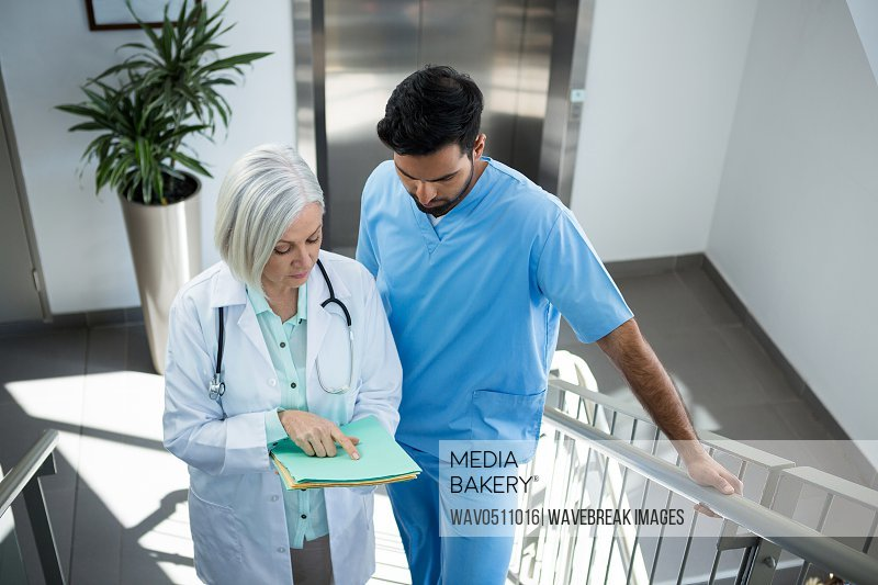 Doctors discussing over report while standing on stairs in hospital