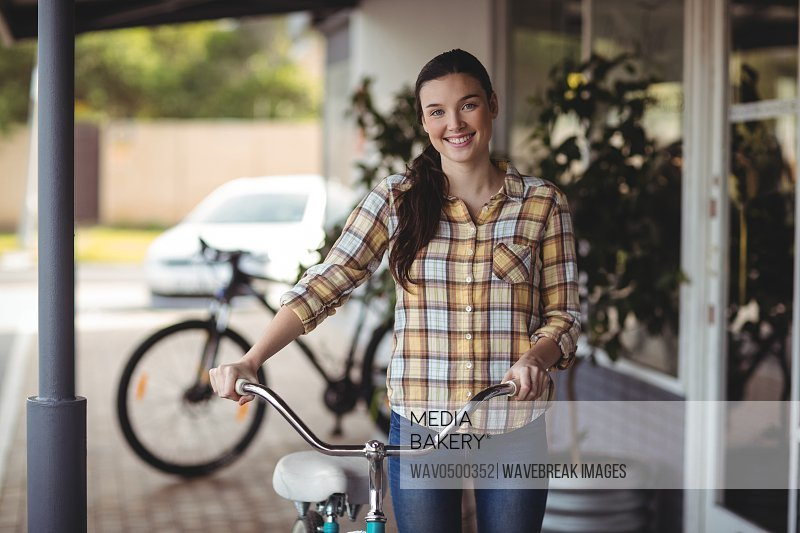 Smiling women standing with bicycle outside the cafeA�
