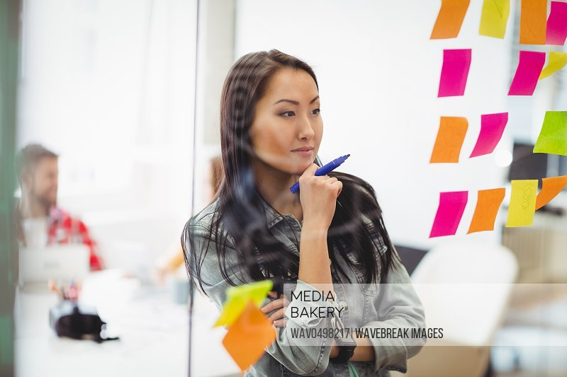 Female photo editor looking at multi colored sticky notes on glass in meeting room at creative office