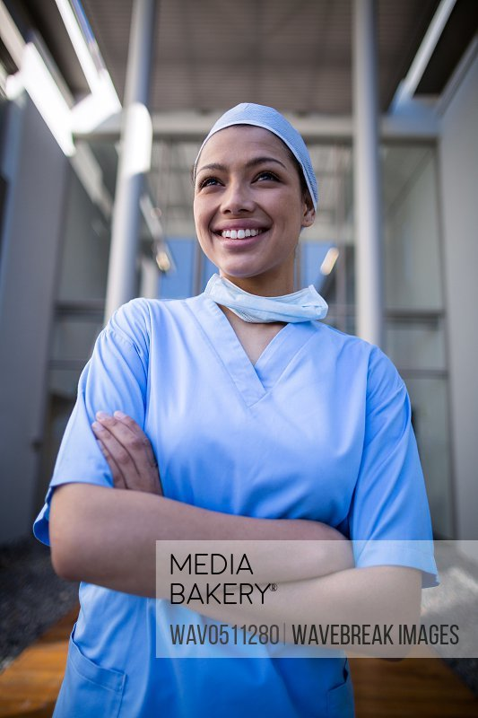 Female surgeon standing with arms crossed in hospital corridor