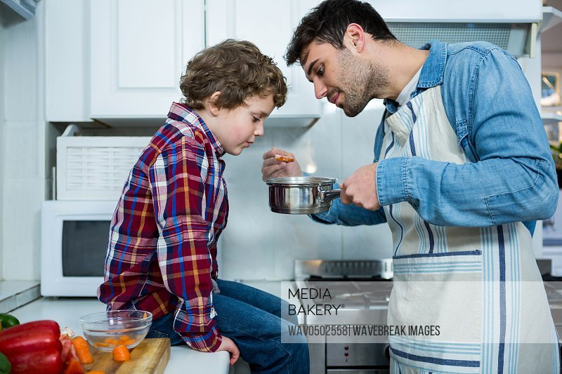 Father and son cooking food together in the kitchen