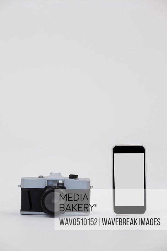 Camera and smartphone against grey background