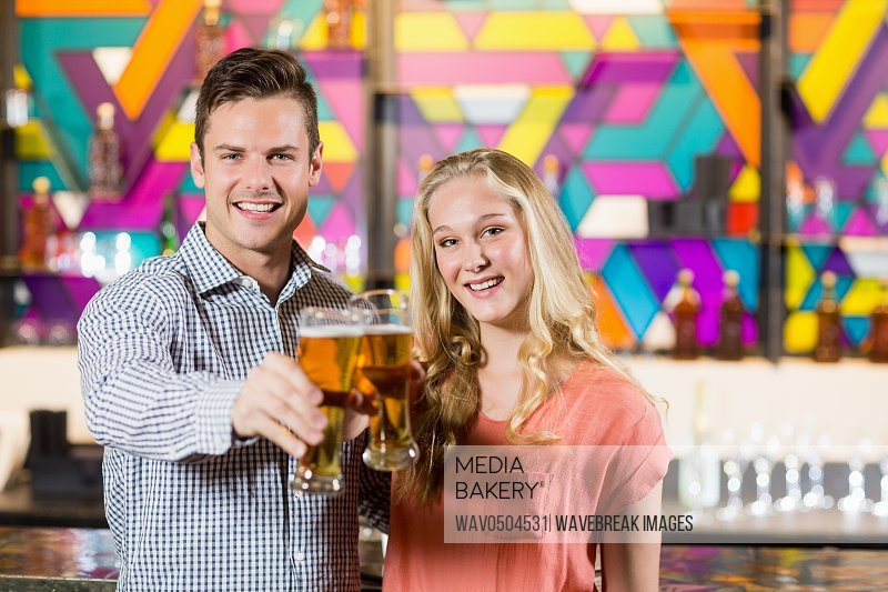 Portrait of smiling couple showing a glass of beer in bar