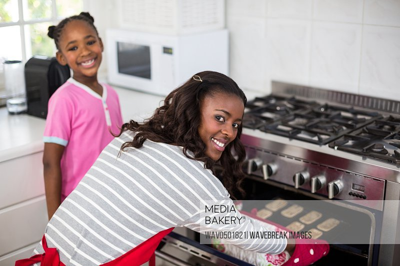Mother putting baking tray in oven at kitchen
