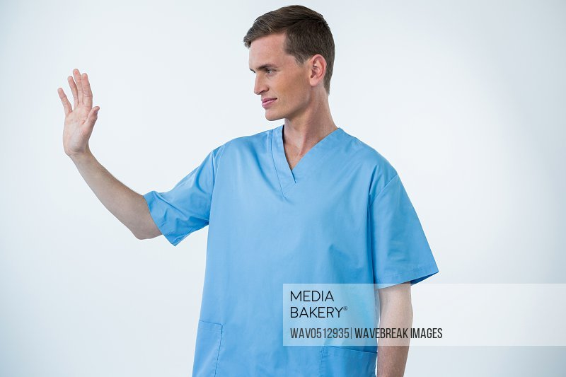 Male nurse touching an invisible screen against white background