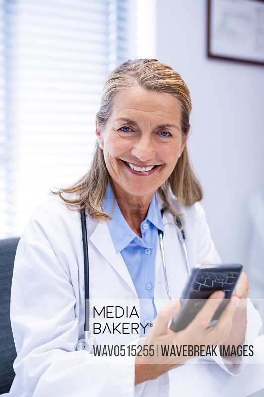 Portrait of female doctor using mobile phone