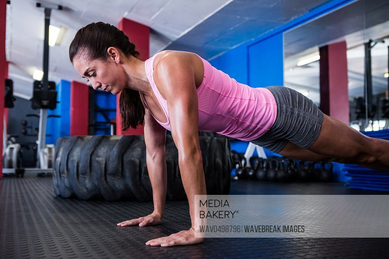 Athlete woman doing push-ups in gym