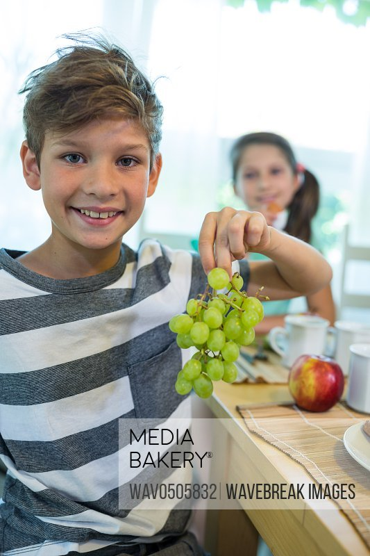 Boy holding a bunch of grapes while having breakfast at home