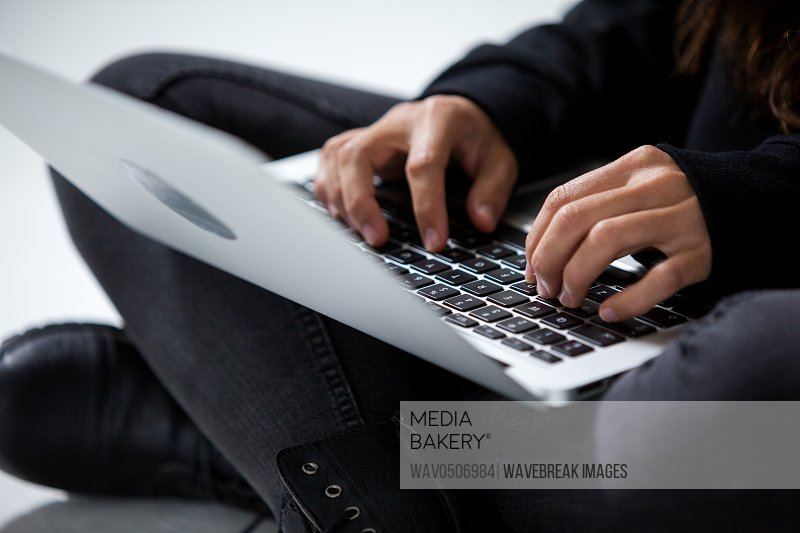 Close-up of hacker using a laptop against white background