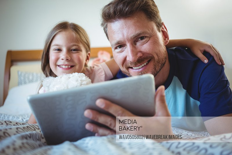 Father lying with daughter on bed and using digital tablet at home