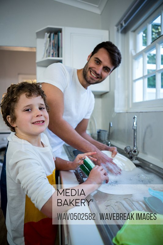 Portrait of son helping father in washing utensils in the kitchen sink