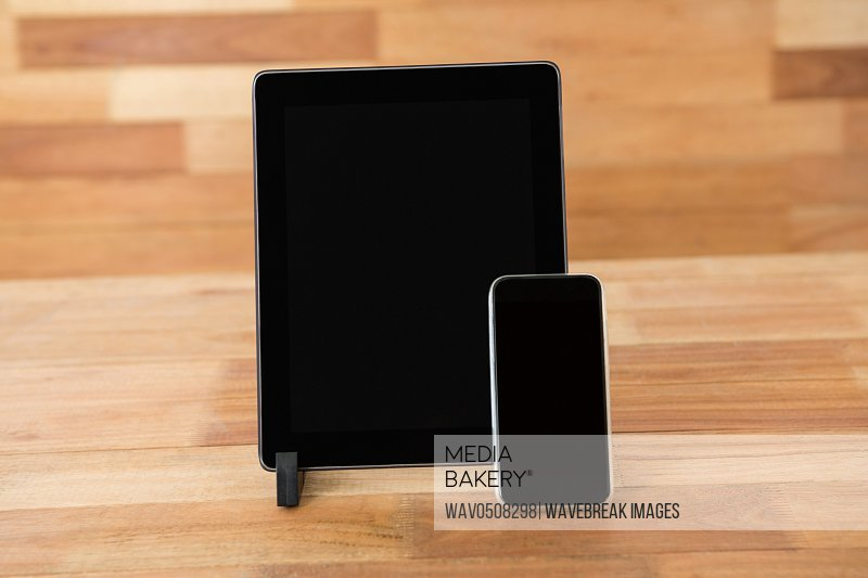 Digital tablet and mobile phone on wooden table