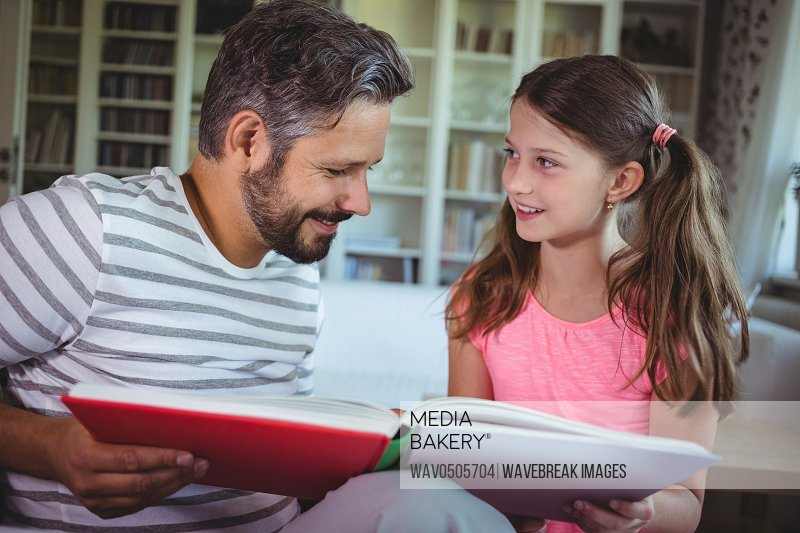 Smiling father and daughter looking at photo album in living room at home