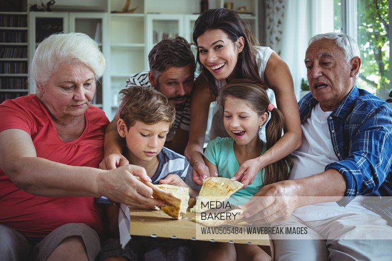 Multi-generation family having pizza in living room at home