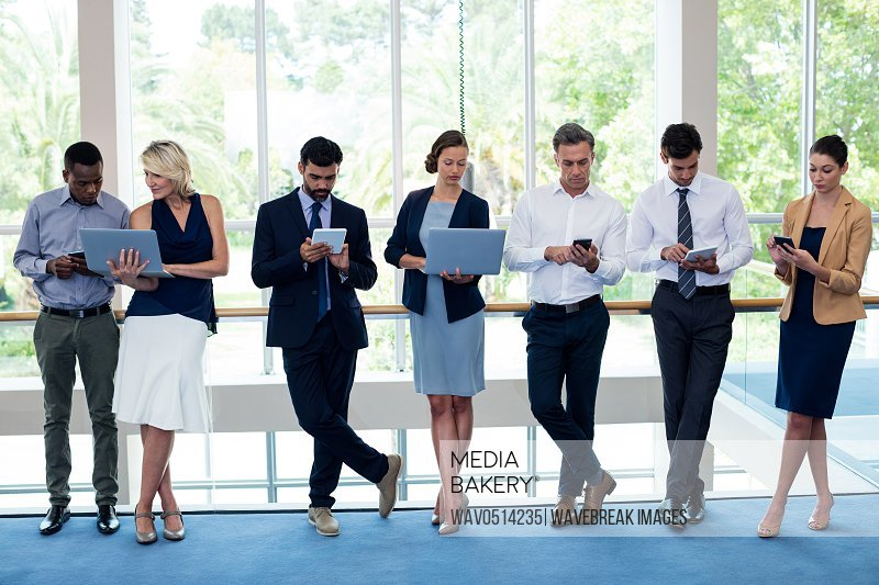 Business executives using mobile phone digital tablet laptop