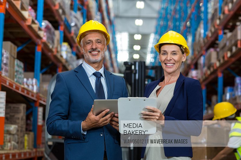 Warehouse manager and client smiling in warehouse
