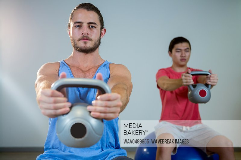 Men exercising with dumbbells on exercise ball in gym