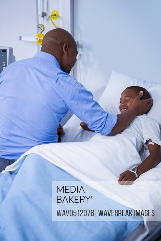 Male doctor consoling patient during visit in ward at hospital