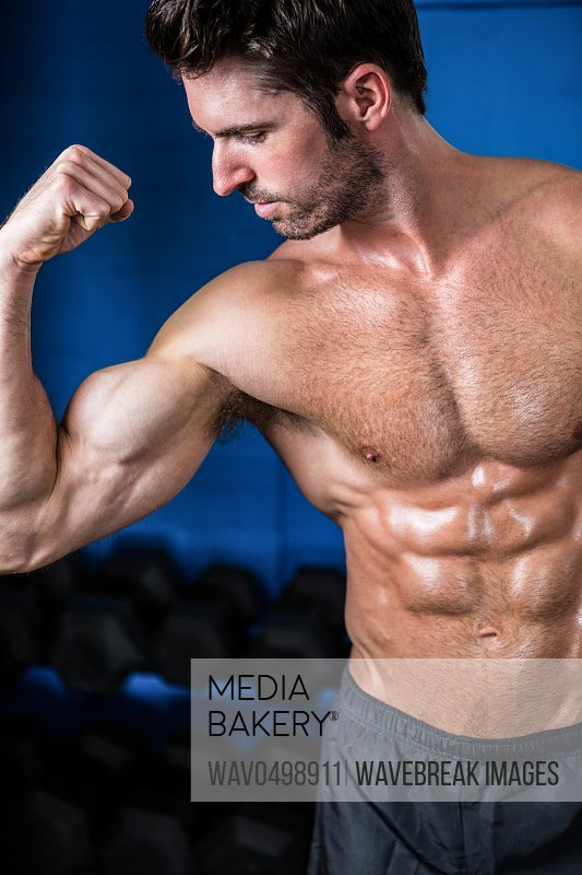 Shirtless athlete flexing muscles while standing in gym