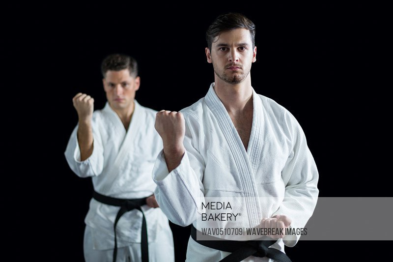 Two karate fighters performing karate stance against black background
