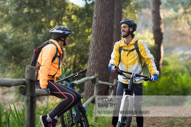Biker couple interacting with each other in countryside forest