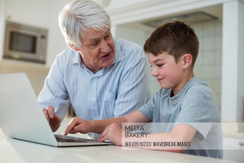 Grandson using laptop with grandfather