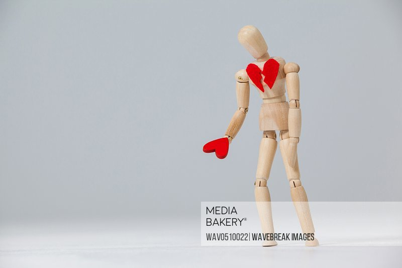 Wooden figurine with a broken heart and holding a red heart against white background