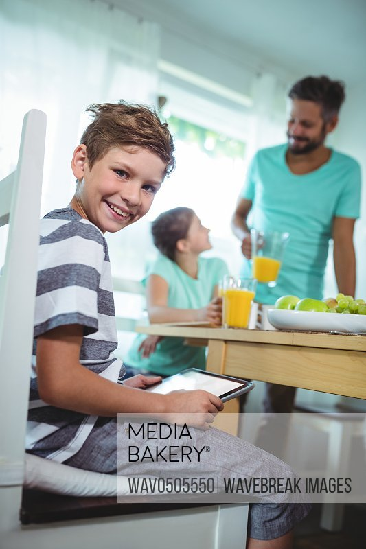 Portrait of boy using digital tablet with breakfast on table at home
