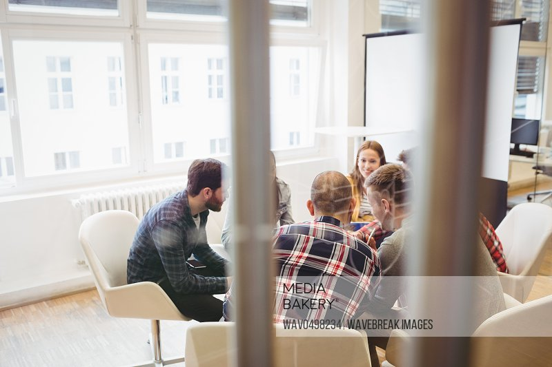 Business people discussing in meeting room seen through glass