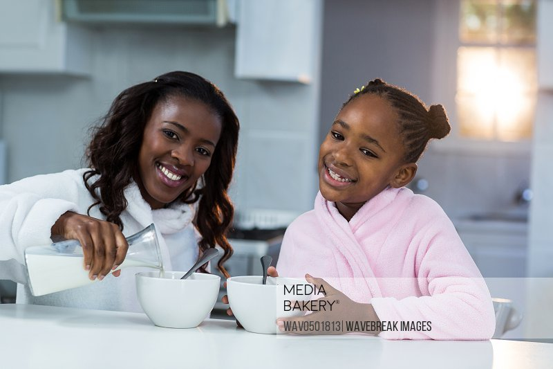 Portrait of mother and daughter pouring milk in a bowl at kitchen