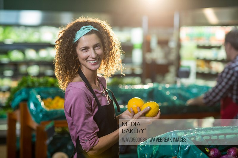 Portrait of smiling female staff holding fruits in organic section of supermarket