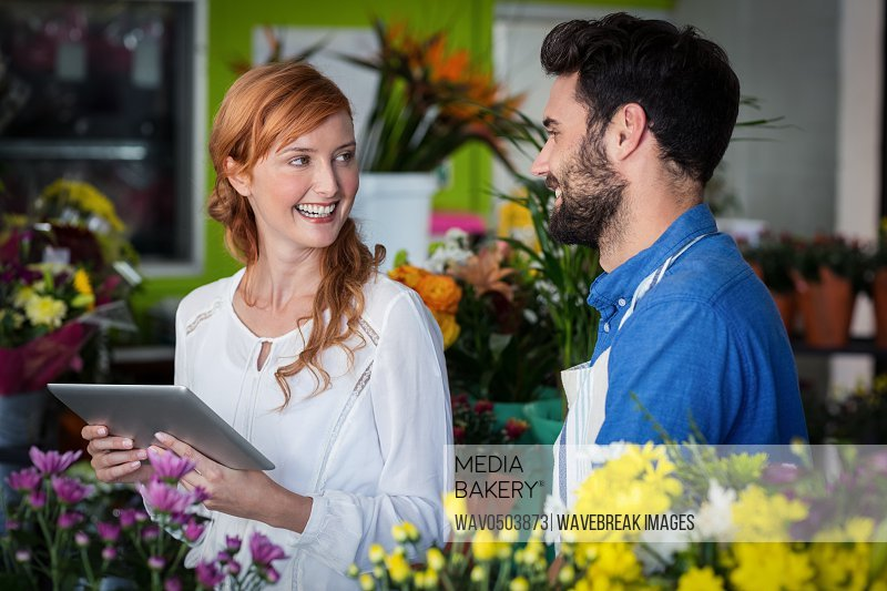 Couple standing with digital tablet in the flower shop