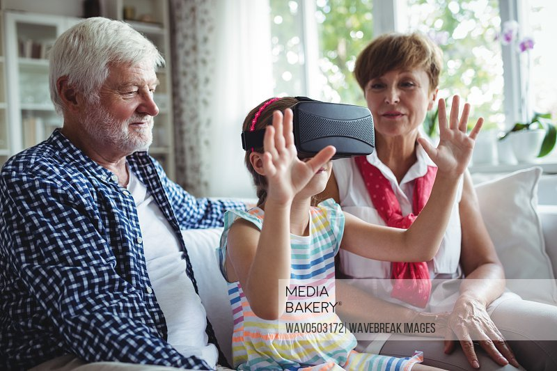 Granddaughter using virtual reality headset with her grandparents in living room at home