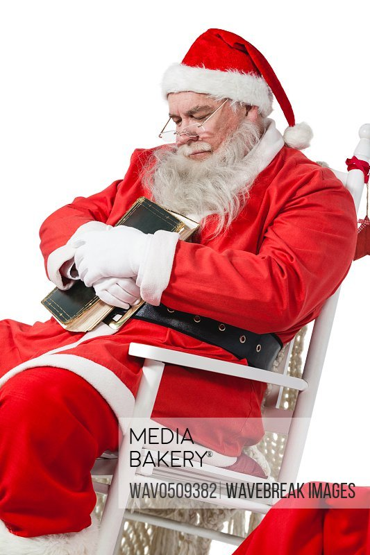 Santa claus holding bible while relaxing on chair