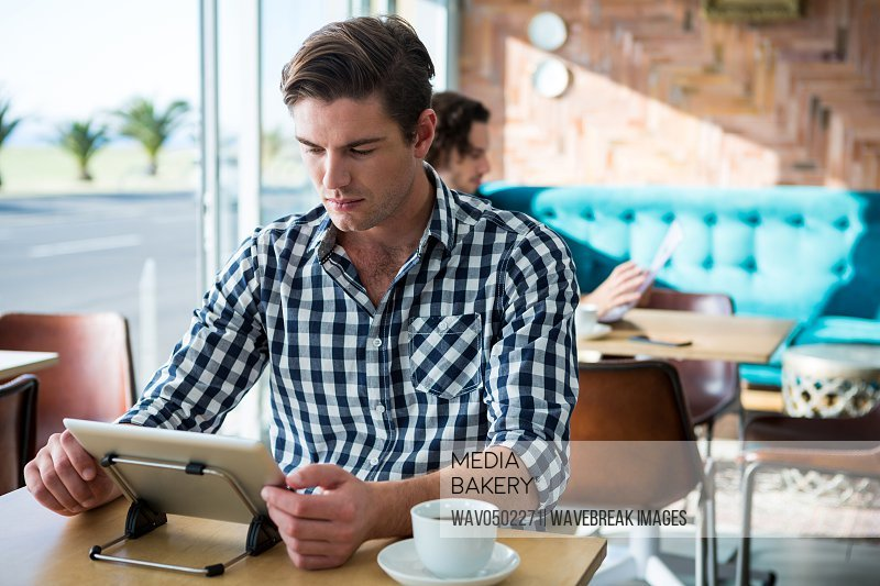 Man sitting at table and using digital tablet in coffee shop