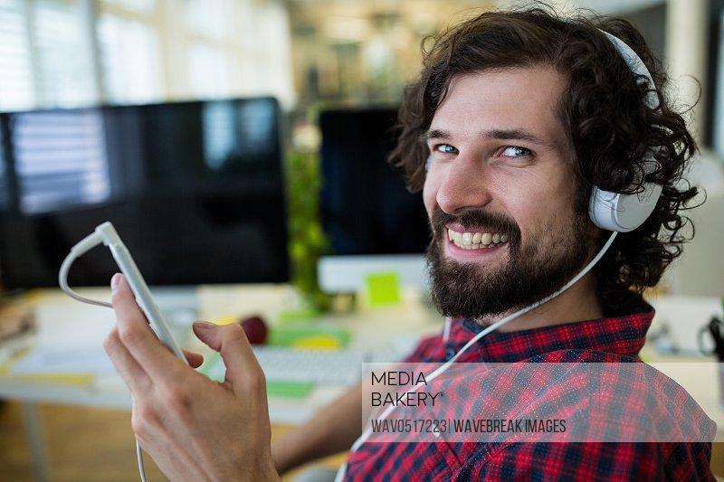 Portrait of smiling business executive listening to music on mobile phone