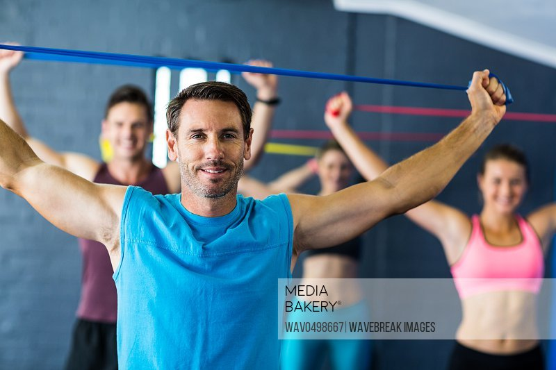 Portrait of male instructor with athletes in fitness studio