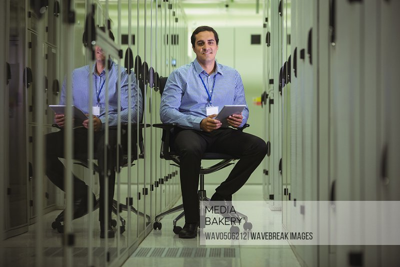 Portrait of technician siting on chair and using digital tablet in server room