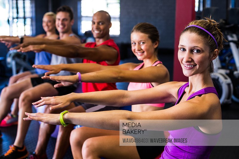 Portrait of smiling friends doing stretching exercise in gym