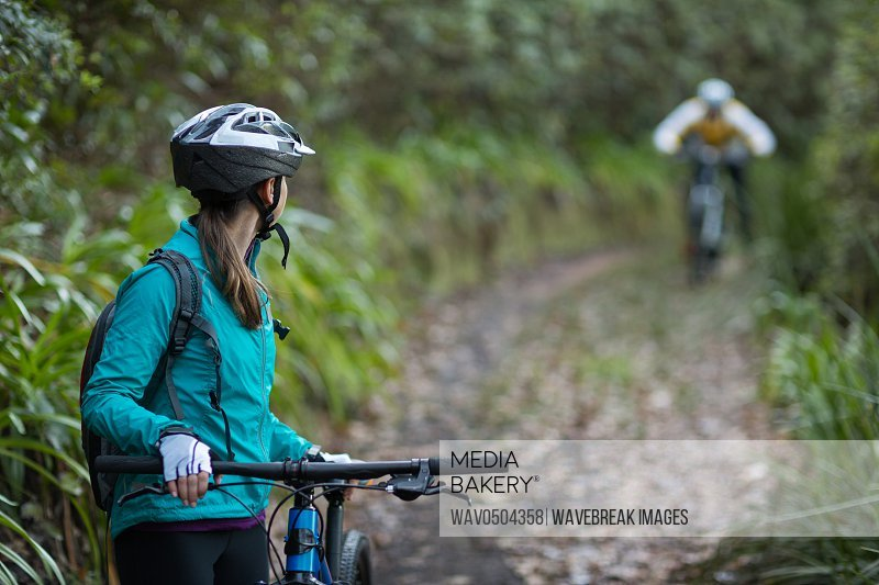Female biker waiting for male biker in countryside forest