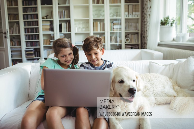 Children using laptop while sitting on a sofa at home
