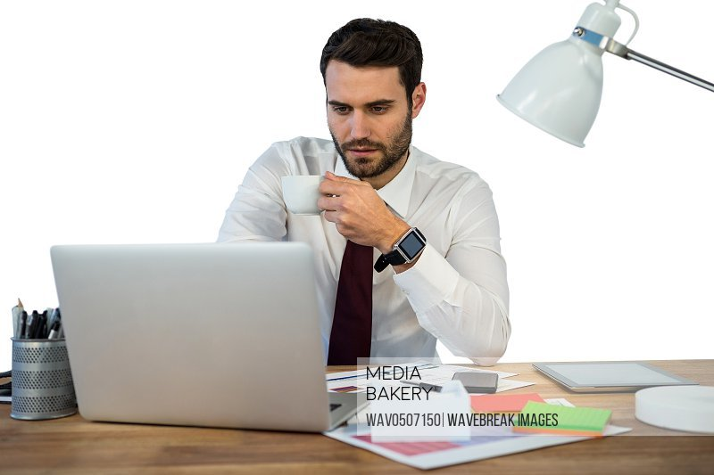 Businessman working on laptop in office while having coffee against white background