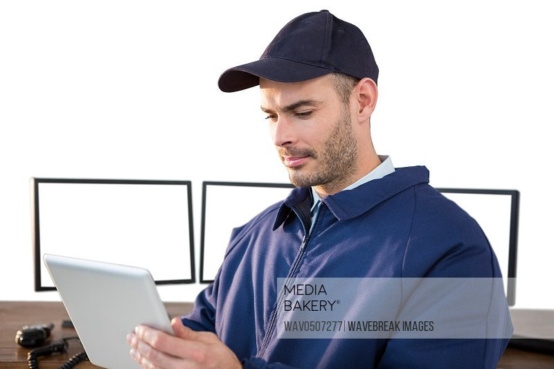 Security officer using digital tablet at desk with computer in background