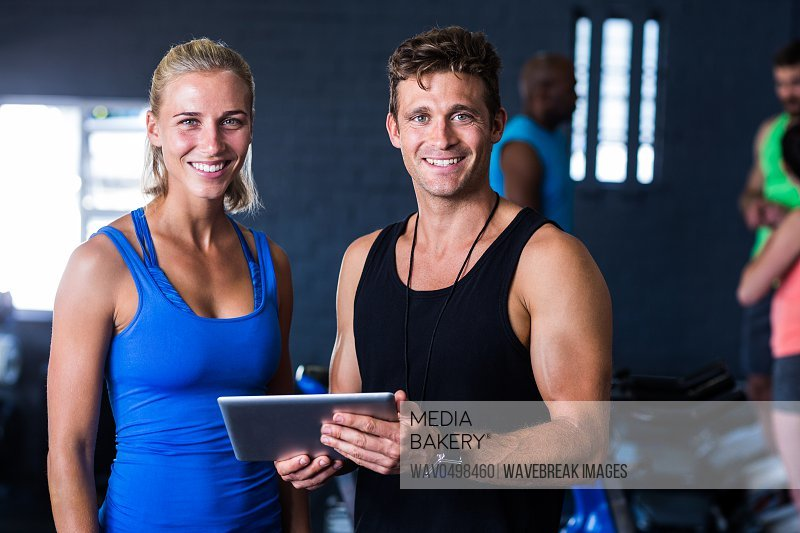Portrait of smiling friends with digital tablet while standing in gym