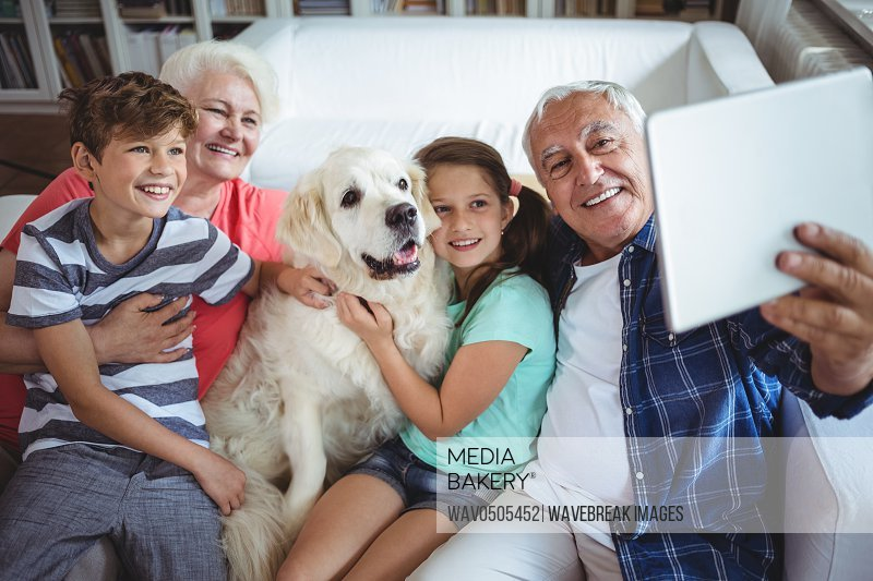 Grandparents and grandchildren sitting on sofa and taking a selfie with digital tablet