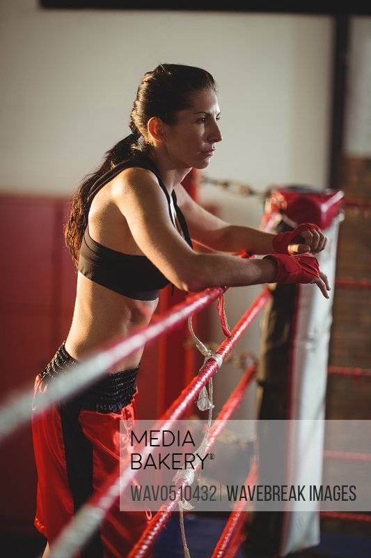 Thoughtful female boxer standing in boxing ring