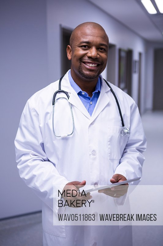 Portrait of male doctor standing with digital tablet in corridor at hospital