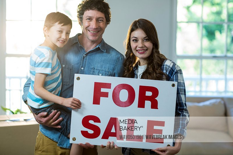 Couple standing and holding sold sign at home