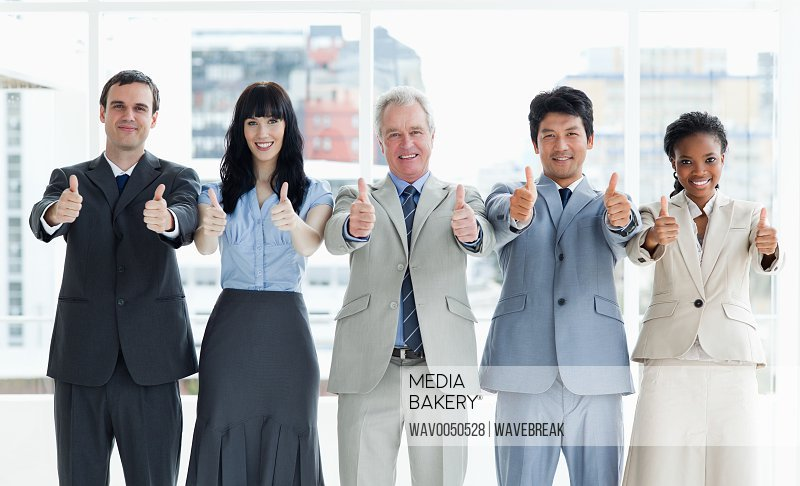 Smiling business people showing their approval with their thumbs up