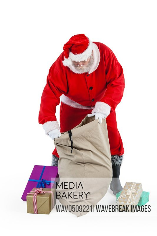 Santa claus filling gift boxes in the sack